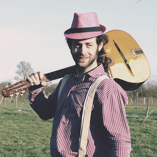Fanfare le musicien avec sa guitare sourit dans la ferme