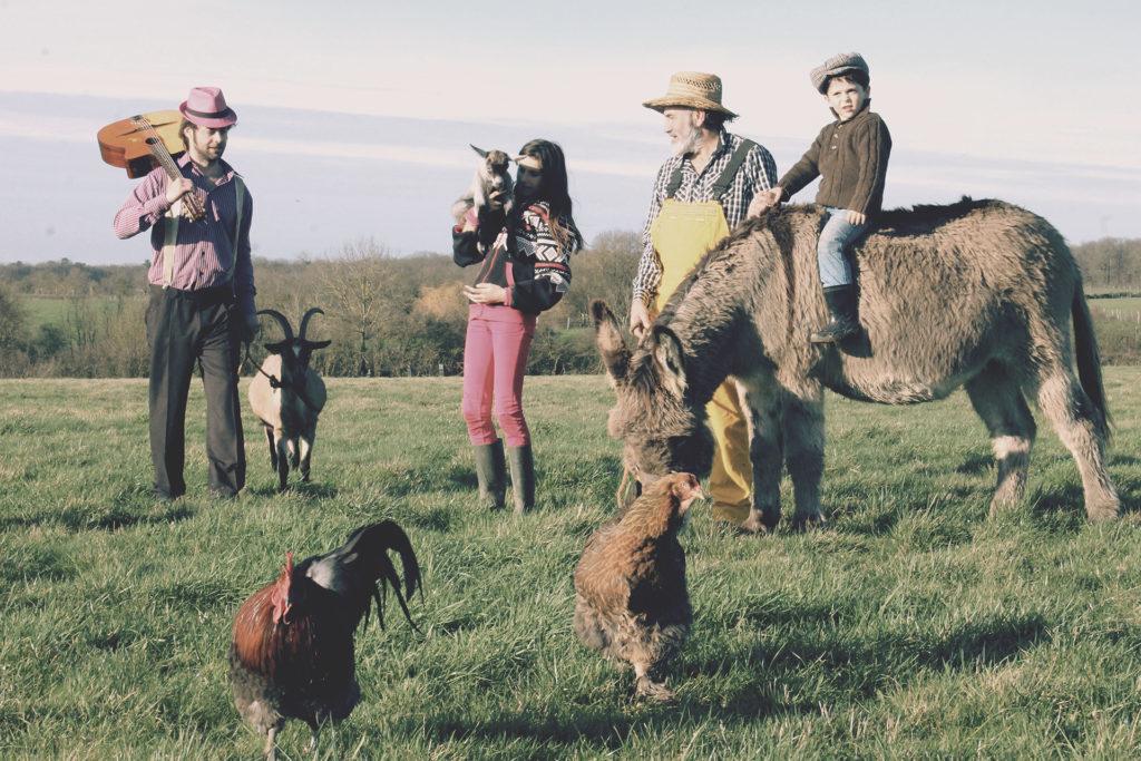 Le fermier Tiligolo, le musicien Fanfare et les enfants se promènent dans un champ avec les animaux de la ferme